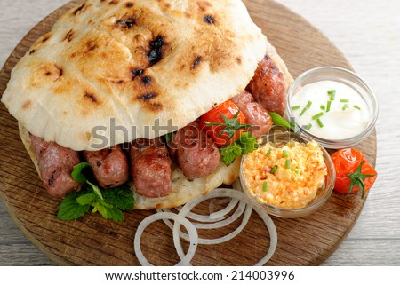 Cevapcici, a small skinless sausage cooked on the barbecue and served with: Lepinja bread, pickled red capsicum and Kajmak cheese. This dish is popular all over the Balkans, with tourists and locals.  - stock photo
