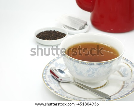 ceylon tea in antique porcelain cup with spoon on white background