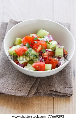 Chachamber, an Indian salad made from cucumbers, tomatoes and onions with cilantro, served on a napkin. - stock photo