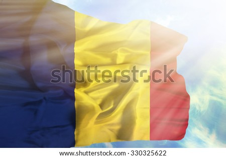 Chad waving flag against blue sky with sunrays - stock photo