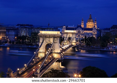 Chain Bridge and St Stephen Basilica at night, Budapest. Visible boats movement on the Danube River - stock photo