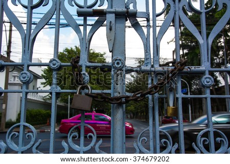 chain link fence and metal door with lock. - stock photo