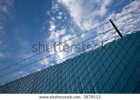 Chain link fence with privacy screens and barbed wire - stock photo