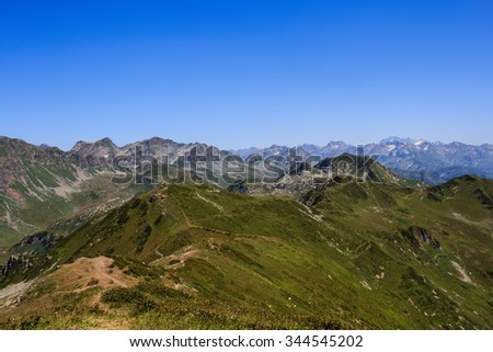 chain of high rocky mountains and green alpine meadows with sandy trails in caucasus mountains in Abkhazia Georgia - stock photo