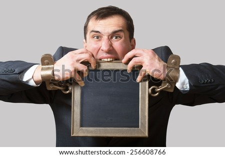 Chained businessman with a board