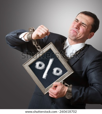 Chained businessman with a board - stock photo