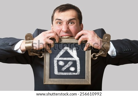 Chained businessman with a board, mortgage concept - stock photo