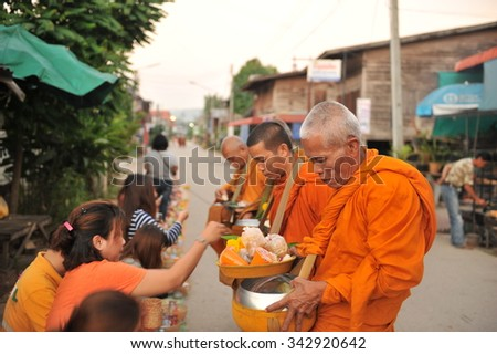 chaingkhan in loie province, Thailand - november 17 :street life in  chaingkhan in loie province on november17, 2015. give alms to a Buddhist monk sticky rice
