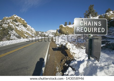 Chains Required sign after fresh snowfall along Highway 33 north of Ojai, California - stock photo