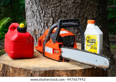 chainsaw and canister of gasoline and motor oil - stock photo