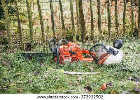 Chainsaw and pruning handsaw lying in the garden. - stock photo