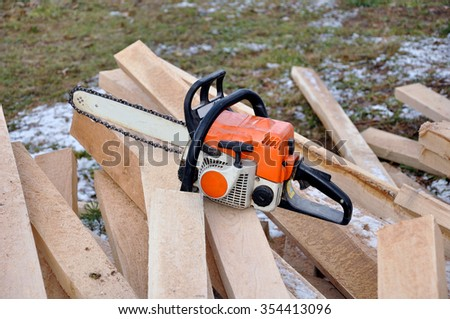 Chainsaw In The Forest. Professional chainsaw on pile of cut wood. Chainsaw on heap firewood outdoors. - stock photo