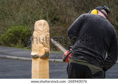 Chainsaw Sculptor at work / The making of an owl sculpture by a chainsaw sculptor here in the midway stage - stock photo