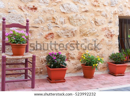 Chair and flower pots decorate home exterior in narrow Spanish traditional village streets