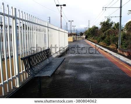 Chair at platform of  Blackburn railway station for waiting train for go to Flinders Street Railway Station and train is coming after raining. - stock photo