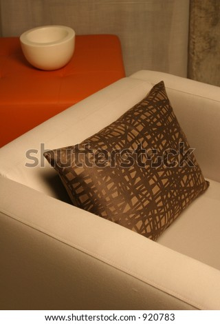 chair detail with designer pillow (image contains some noise) - stock photo