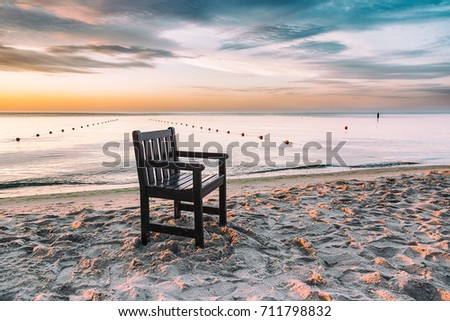 Chair left on the beach at sunrise