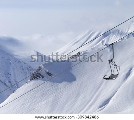 Chair lift and mountains in fog. Caucasus Mountains, Georgia, ski resort Gudauri. - stock photo