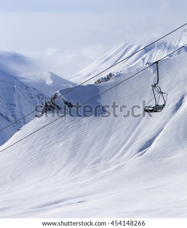 Chair lift at ski resort and off piste slope. Caucasus Mountains, Georgia, region Gudauri. - stock photo