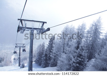 Chair lift between beautiful firs in winter mountains forest - stock photo