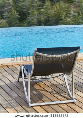 Chair on swimming pool deck - stock photo
