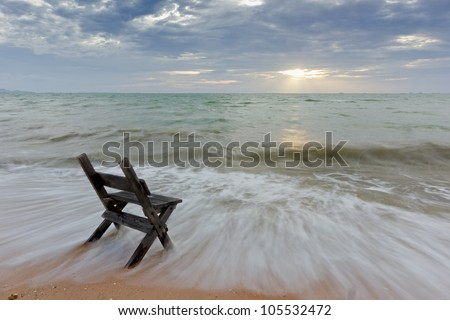 Chair on the sea sand with long speed shutter... lonely and waiting - stock photo