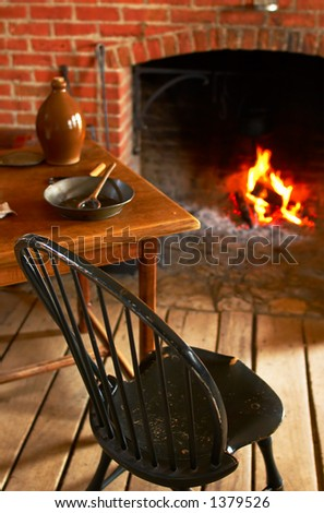 Chair, table, & fireplace in kitchen at Fort Snelling in 1820s. More with keyword Series08E. - stock photo