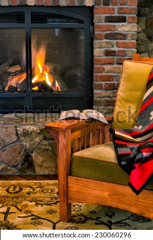 Chair with a book by a cozy fireplace. Style is rustic elegance, lodge, upscale cabin