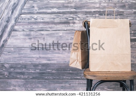 Chair with blank shopping bags on wooden plank background. Mock up - stock photo
