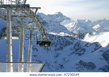 Chairlift carrying skiers and snowboarders - stock photo