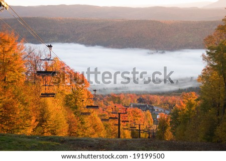 Chairlift climbing on a fall mountain slope with morning mist in the valley - stock photo