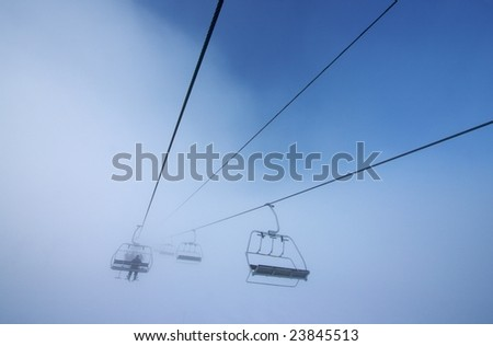 Chairlift disappearing into fog