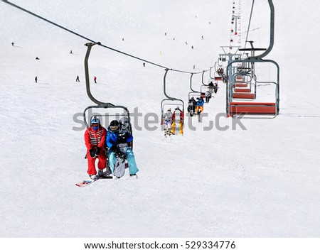 Chairlift (ski lift) transport skiers and snowboarders up a snowy downhill at winter ski snow Alpine resort, active seasonal outside sports background