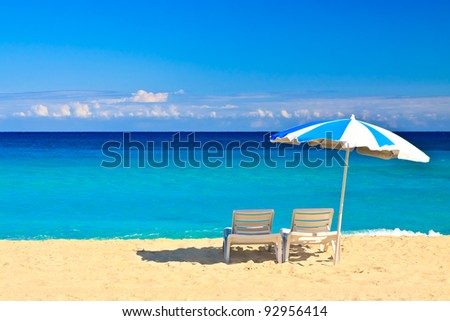 Chairs and parasol on the beautiful cuban beach of Varadero with a clear blue sky useful to add text - stock photo