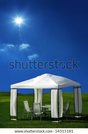 chairs and table under white picnic tent on green grass - stock photo