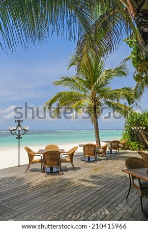 Chairs and tables of a tropical restaurant on the beach right beneath the blue ocean. Palm trees framing the scene, Maldives islands. - stock photo