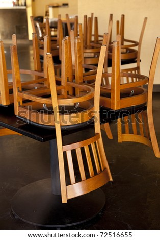 Chairs and tables stacked in a closed restaurant.