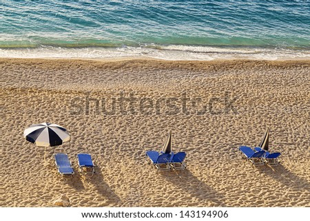 chairs and umbrella on a beach - stock photo