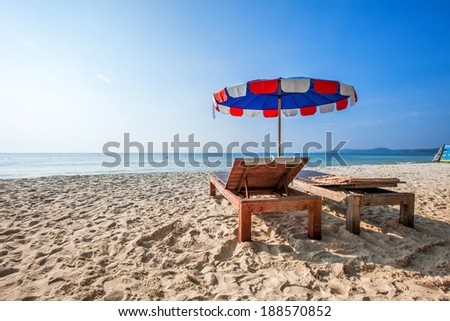 Chairs and umbrella on a beautiful tropical beach. - stock photo