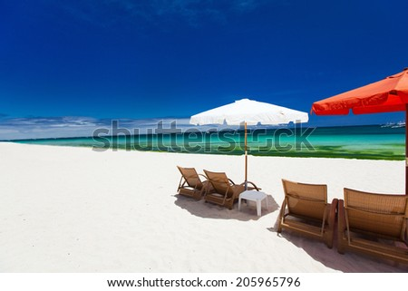 Chairs and umbrellas on a beautiful tropical beach with white sand and clear turquoise ocean at exotic island in Philippines