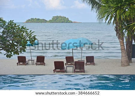 Chairs and umbrellas on the beach surrounded with trees. Green island in background. - stock photo