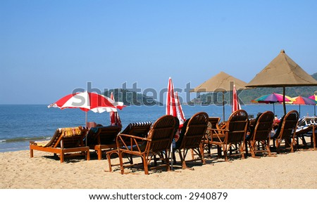 Chairs and umbrellas on the sand tropical beach - stock photo