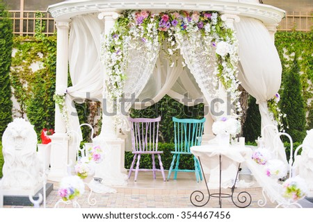 chairs for bride and groom in decorated arbor