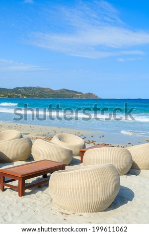 Chairs in a beach bar with wooden table on white sand in Porto Giunco bay, Sardinia island, Italy
