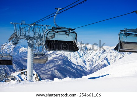 Chairs on chairlift ropeway in winter mountains - stock photo
