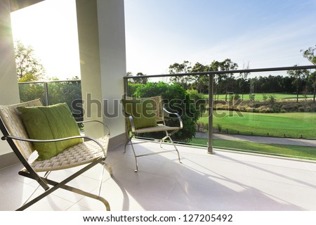 Chairs on modern balcony overlooking a gold course - stock photo
