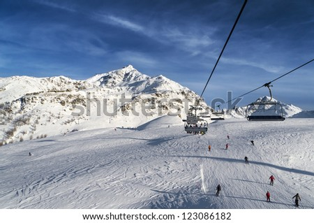 chairs on ski lift above a slope in high mountain - stock photo