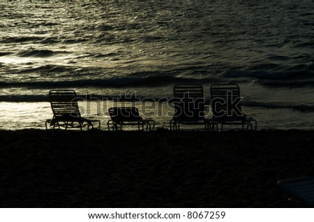 Chairs on the beach, backlit - stock photo