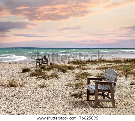 Chairs On The Beach Looking Out At The Mackinaw Straits And Lake Huron At Sunset The Straits Of Mackinac, Michigan, USA - stock photo