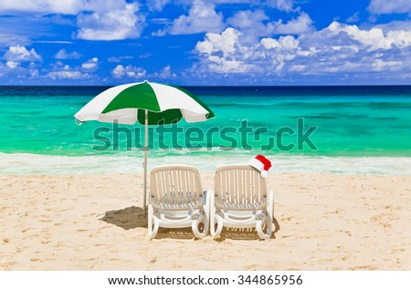 Chairs on tropical beach and Santa Claus red christmas hat - vacation background